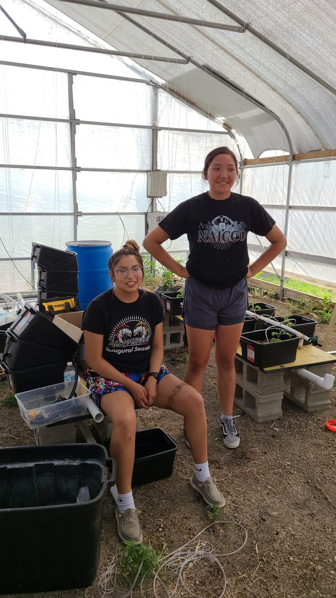 Josette Pretty Sounding Flute sits next to Jesse Estes (standing) in front of the hydroponics setup.