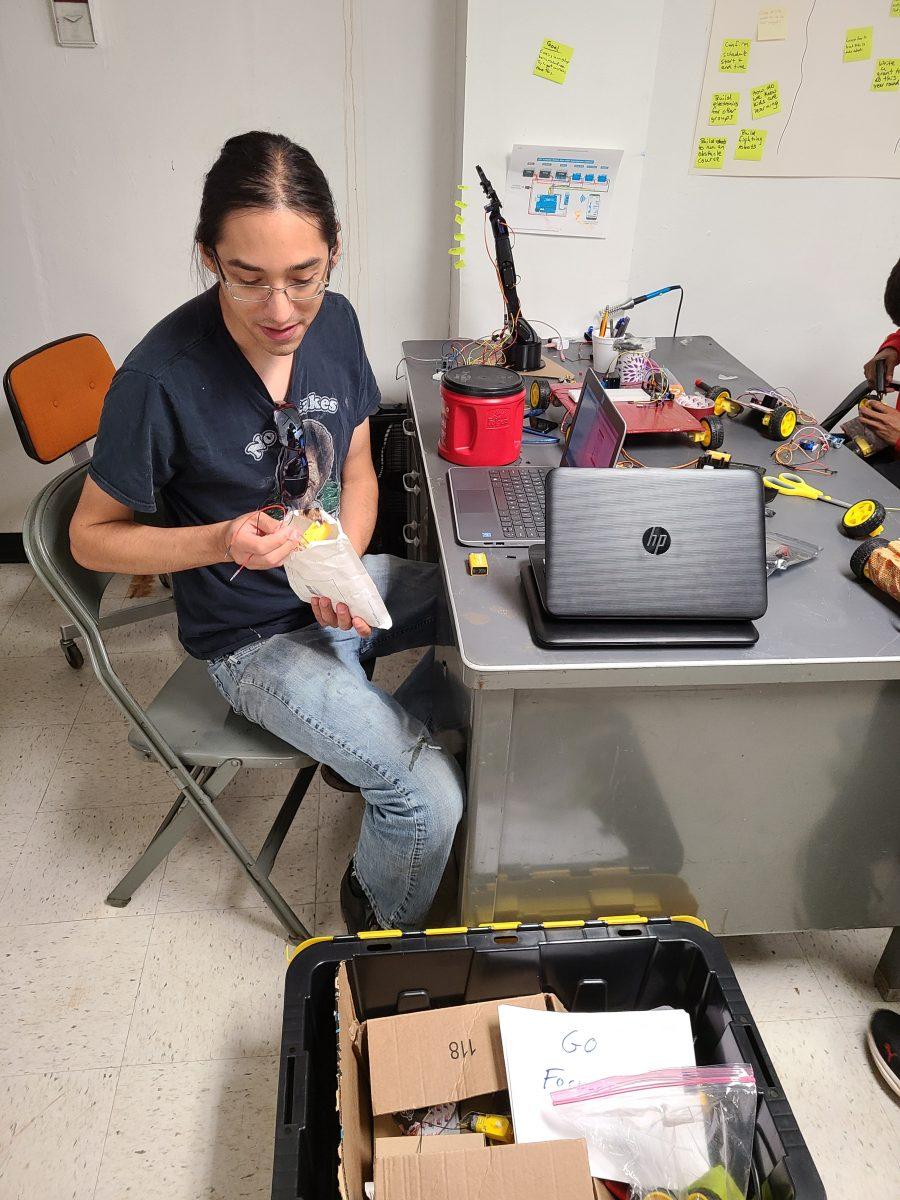 Tokala Estes picks some robot parts out of a bag.