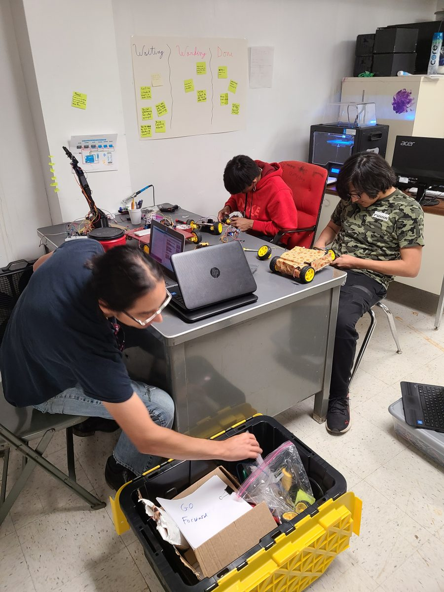 The three people work independently in their robots at the same table.